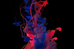 颜色油漆下落在水中 打旋的墨水在水面下 免版税库存图片