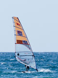 颜色田径服的年轻运动员行使在风帆冲浪的  库存图片