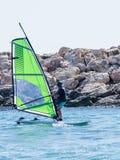 颜色田径服的年轻运动员行使在风帆冲浪的  免版税图库摄影