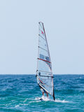 颜色田径服的年轻运动员行使在风帆冲浪的  库存照片