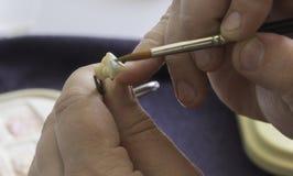 颜色的处理和选择一条牙齿假肢的在一个牙齿实验室 免版税库存照片