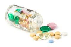 颜色药片流洒一个透明瓶 免版税图库摄影