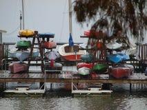 颜色被存放的小游艇船坞小船在惨淡的灰色下雨天 图库摄影