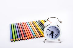 颜色铅笔和闹钟 图库摄影