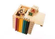 颜色铅笔在木字母表块箱子前面安排 免版税图库摄影