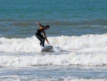 颜色防水衣服的女孩行使在冲浪的在委员会 库存照片