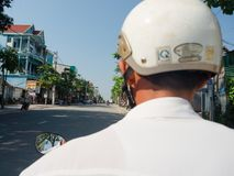 颜色,越南- 2017年9月13日:关闭有一件白色盔甲的未认出的人,骑在街道的一辆摩托车  免版税库存图片