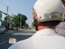 颜色,越南- 2017年9月13日:关闭有一件白色盔甲的未认出的人,骑在街道的一辆摩托车  库存图片