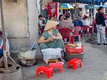 颜色,越南- 2017年9月13日:卖食物的街道的未认出的妇女,位于颜色在越南 免版税库存图片