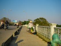 颜色,越南- 2017年9月13日:过桥梁和运载在她的肩膀在的未认出的妇女食物 免版税图库摄影