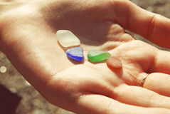 颜色玻璃在海滩的一只女孩手上 免版税库存图片