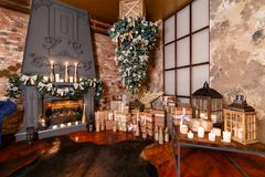 颠倒供选择的树在天花板 浆果装饰霍莉家留给槲寄生多雪的结构树白色冬天 在顶楼内部的圣诞节对砖墙 免版税库存照片