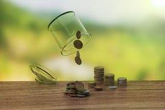颠倒瓶子在木backgro的硬币 图库摄影