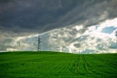 暴风云和电定向塔在麦田 免版税库存照片