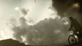 暴风云背景的单独自行车骑士在山 股票录像