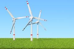 风力场、套反对蓝天的风轮机和绿草 库存图片
