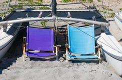 2风化了躺椅和一条小船在沙子在佛罗里达海滩 免版税库存照片