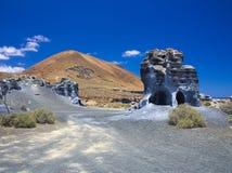 风化蓝色岩石形成普莱诺de El Mojon以一个火山的锥体为背景,蓝天的侵蚀 免版税图库摄影
