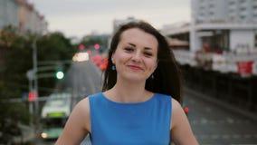 风吹长的黑发美丽的少妇 愉快,微笑的女孩站立在桥梁的和神色在照相机 4K 影视素材
