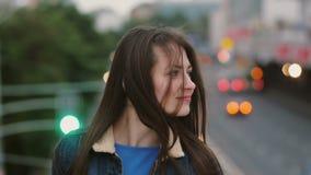 风吹长的头发美丽的少妇 站立在桥梁的微笑的女孩晚上和神色在照相机 4K 影视素材