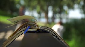 风在公园,企业概念转动开放笔记本谎言页在木扶手栏杆的 股票视频