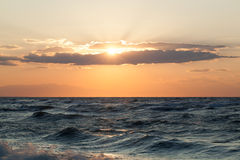 风大浪急的海面和sunsetr在它 库存照片