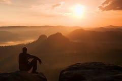 黑风夹克的游人坐锋利的岩石并且观看入五颜六色的有薄雾的谷轰鸣声 在岩石mountai的晴朗的春天破晓 免版税库存照片