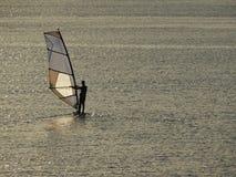 风帆冲浪在与风平浪静的日落 库存照片
