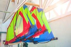 风帆冲浪的不同的风帆在谷仓垂悬 免版税库存照片