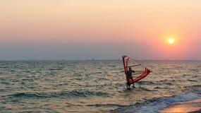 风帆冲浪者在日落的海 库存图片