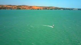 风帆冲浪者在有泡沫似的踪影的绿松石海洋航行 股票视频