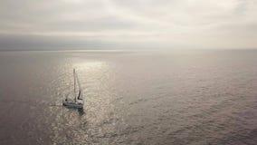 风帆游艇在金黄海,当在平衡天空空中风景的美好的日落时 股票录像