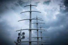 风帆现代游艇帆柱反对剧烈的多云天空的 库存图片