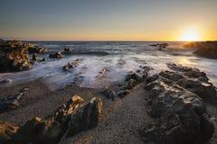 风平浪静的美好的充满活力的日落风景图象反对岩石的 库存图片