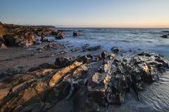 风平浪静的美好的充满活力的日落风景图象反对岩石的 免版税库存图片
