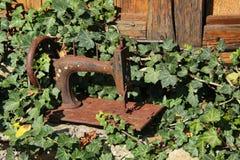 风景一台老手工缝纫机的生锈的船身的照片在老庭院和老木墙壁的绿叶的中 库存照片