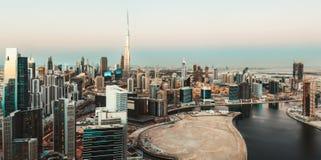风景空中地平线:迪拜` s与现代摩天大楼的企业海湾日落的 免版税库存图片