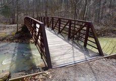 风景红色金属和木桥在一条小河在森林里 免版税库存照片
