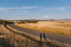 风景观点的美好的托斯卡纳领域、空的路和人 库存照片