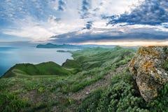 风景 在俯视海的绿色山上面的日落  库存图片