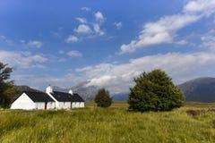 风景Glencoe的逗人喜爱的矮小的白色房子 免版税库存照片