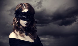 风暴天空背景的美女。 图库摄影