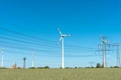 风汽机和电源线在一个晴天 库存照片
