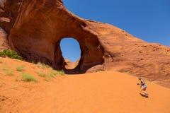 风的耳朵的女孩 在砂岩腐蚀的坑洼自然曲拱 库存照片