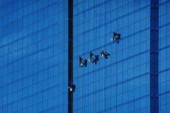 风窗清洁器洗涤在危险摩天大楼的塔的窗口 库存照片