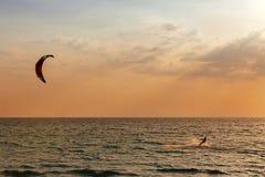 风筝冲浪者航行在日落的海 免版税库存照片