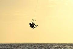 风筝在跃迁的冲浪者剪影 免版税库存照片