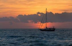 风船与一个现出轮廓的小船航行的日落幻想沿它 免版税库存照片