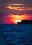 风船和灯塔在剧烈的日落 库存图片