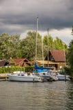 风船在有一个美丽的木房子的一只跳船说谎在背景中 免版税图库摄影